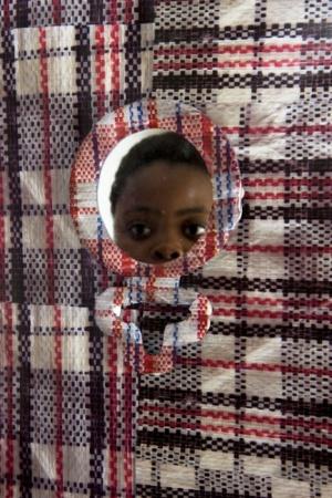 N. Nqaba mirándose al espejo de su instalación 'Unomgcana' / The Tierney Fellowship.-