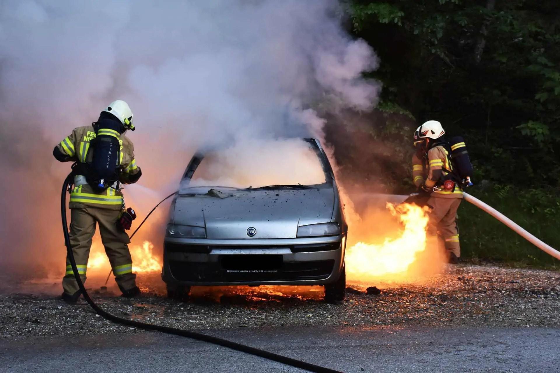 Feuerwehrkräfte löschen einen brennenden Pkw