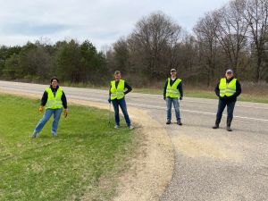 Four Boyceville Education Association volunteers in yellow visibility vests pose, physically distanced, on the highway.