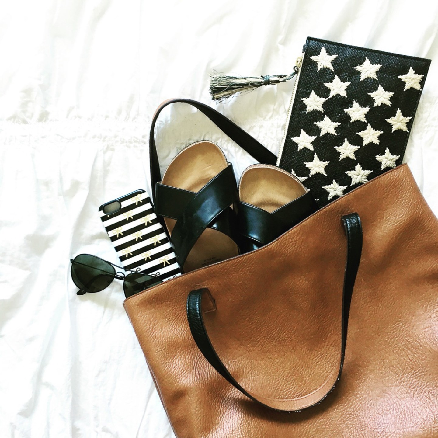 whats-in-my-carry-on-reversible-tote-kayu-star-pouch-black-aviators-criss-cross-slide-sandals