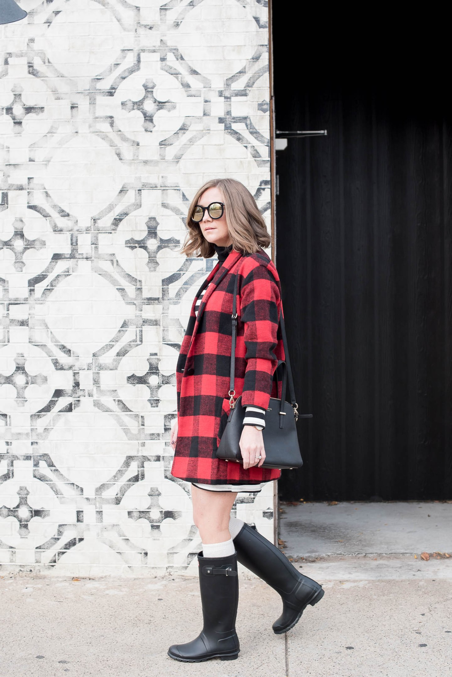 black-and-white-striped-mini-dress-and-red-buffalo-plaid-coat-with-hunter-boots-the-perfect-blogger-wall-for-photos-dowtown-chicago-mild-winter-outfit