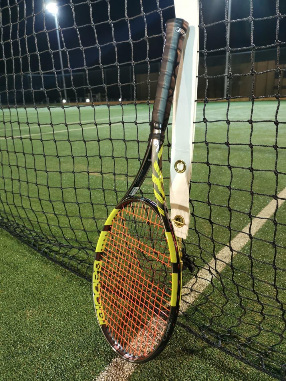 Babolat Pure Aero VS tennis racket leaning against net