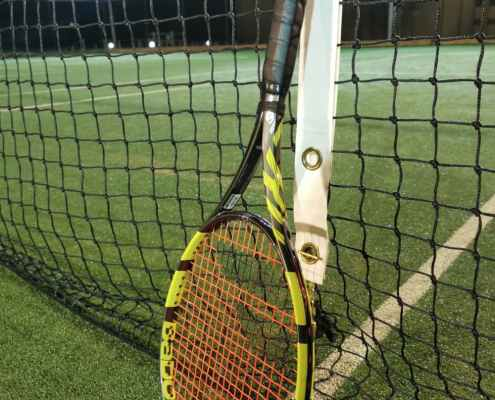 Babolat Pure Aero VS tennis racket leaning against net