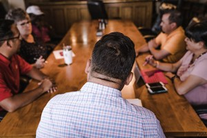 a group of people having a discussion at a table