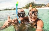 Senior happy couple taking selfie in tropical sea shutterstock_749309983_web