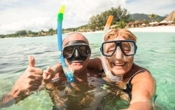 Senior happy couple taking selfie in tropical sea shutterstock_749309983_web
