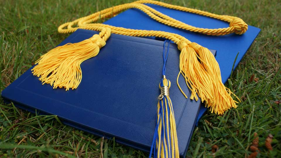 A graduation cap with a degree and tassel on top of it.