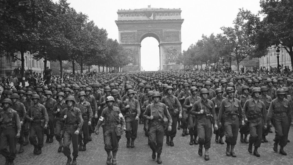 Pennsylvania's 28th Infantry Division march along the Champs Elysees, the Arc de Triomphe