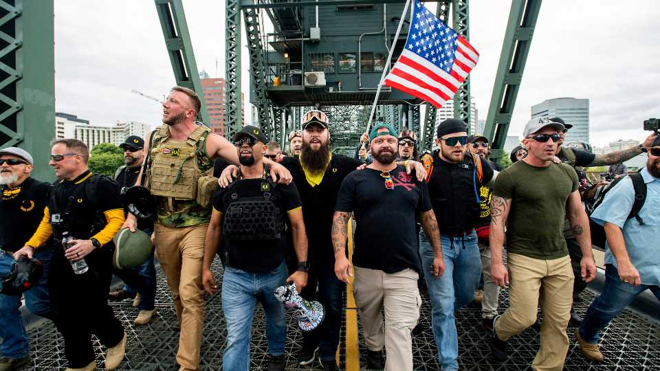 """Members of the Proud Boys and other right-wing demonstrators march across the Hawthorne Bridge during an """"End Domestic Terrorism"""" rally in Portland, Oregon (AP Photo/Noah Berger)"""