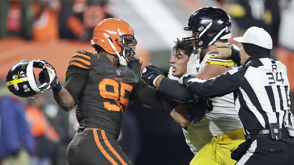 Cleveland Browns defensive end Myles Garrett, left, gets ready to hit Pittsburgh Steelers quarterback Mason Rudolph, second from left, with a helmet during the second half of an NFL football game, Thursday, Nov. 14, 2019, in Cleveland. The Browns won 21-7.