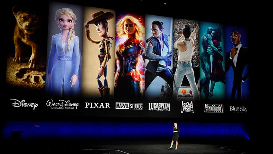 FILE - In this April 3, 2019, file photo characters from Disney and Fox movies are displayed behind Cathleen Taff, president of distribution, franchise management, business and audience insight for Walt Disney Studios during the Walt Disney Studios Motion Pictures presentation at CinemaCon 2019, the official convention of the National Association of Theatre Owners (NATO) at Caesars Palace in Las Vegas. On Tuesday, Nov. 12, Disney Plus launches its streaming service.
