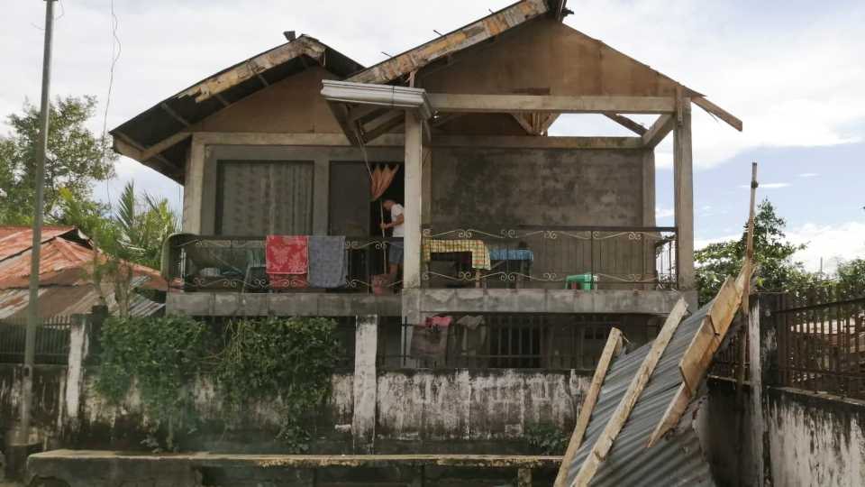 A resident checks his home damaged by Typhoon Phanfone in Ormoc city, central Philippines (AP photo).