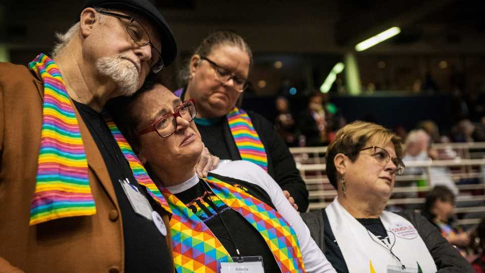 In this Feb. 26, 2019 file photo, Ed Rowe, left, Rebecca Wilson, Robin Hager and Jill Zundel, react to the defeat of a proposal that would allow LGBTQ clergy and same-sex marriage within the United Methodist Church at the denomination's 2019 Special Session of the General Conference in St. Louis, Mo. The 16 United Methodist bishops and advocacy group leaders who negotiated the recent proposal to split the denomination met on Monday, Jan. 13, 2020, to explain their reasoning at an event that was streamed live by United Methodist News Service.