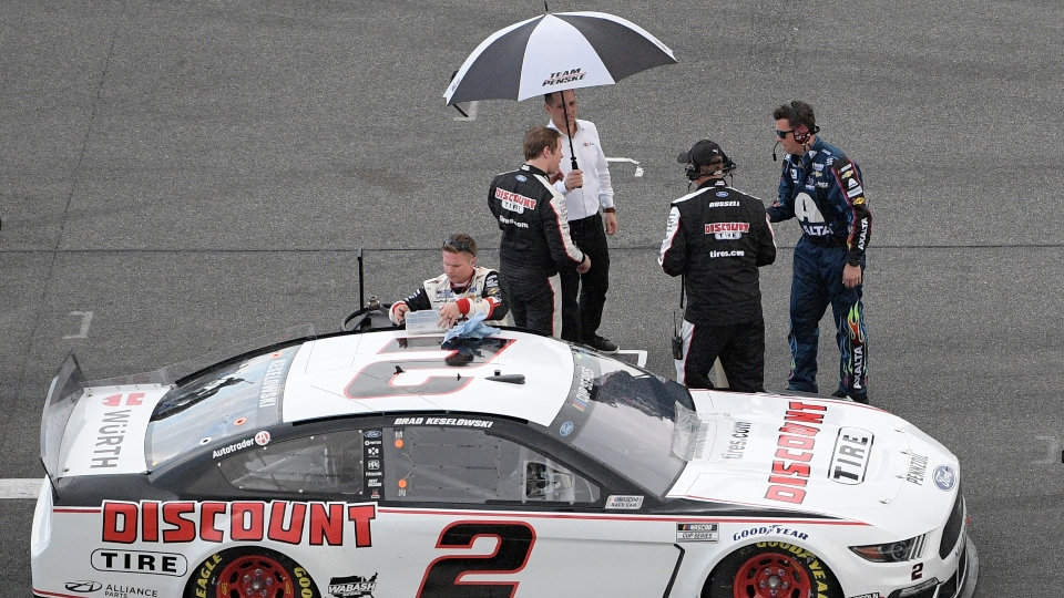 Brad Keselowski stands under an umbrella on pit road as rain forces a red flag during the NASCAR Daytona 500 auto race at Daytona International Speedway, Sunday, Feb. 16, 2020, in Daytona Beach, Fla.