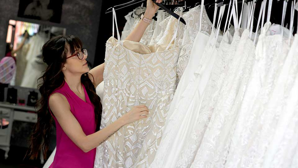 In this Friday, June 21, 2019, photo Assistant manager Brooke Hernandez hangs wedding gowns Friday, June 21, 2019 at Strut Bridal Shop in Tempe, Ariz. Cut-rate prices on websites that sell wedding dresses direct from China put pressure on owner Ann Campeau, who owns four bridal shops in California and Arizona. She has had customers come in after seeing low-end gowns online and expecting to get a dress at a similar price.