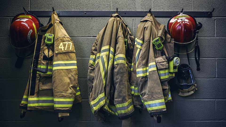 Firefighter gear hanging on a coat rack.