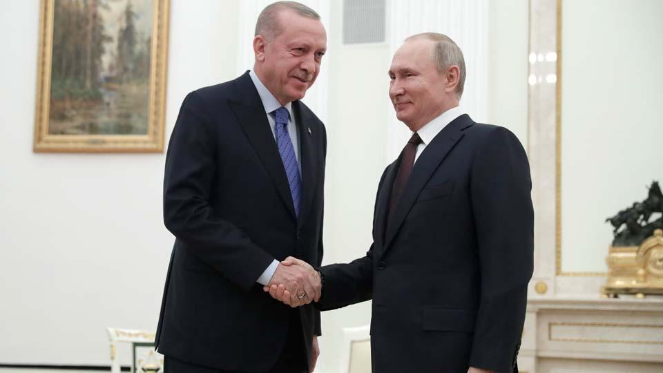 Russian President Vladimir Putin, right, and Turkish President Recep Tayyip Erdogan shake hands