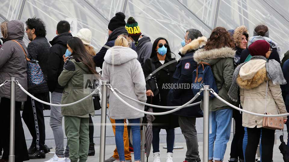 Tourists, some wearing a mask, queue to enter the Louvre museum Friday, Feb. 28, 2020 in Paris. . The world is scrambling to get on top of the new coronavirus outbreak that has spread from its epicenter in China to most corners of the planet. Governments and doctors are presenting an array of approaches as the virus disrupts daily routines, business plans and international travel around the world