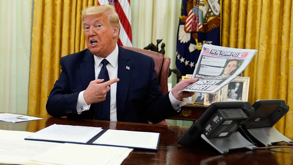 President Donald Trump holds up a copy of the New York Post as speaks before signing an executive order aimed at curbing protections for social media giants