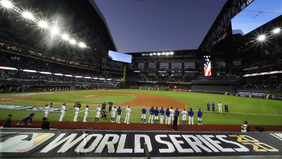 The Los Angeles Dodgers line up during during the national anthem and a fly over before Game 1 of the baseball World Series against the Tampa Bay Rays Tuesday, Oct. 20, 2020, in Arlington, Texas.