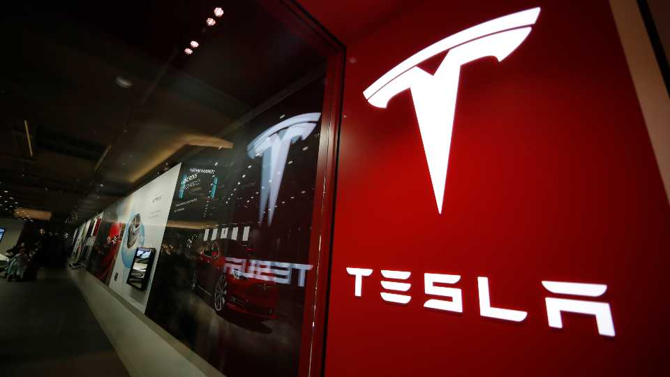 FILE - In this Feb. 9, 2019, file photo, a sign bearing the company logo stands outside a Tesla store in Cherry Creek Mall in Denver. U.S. safety regulators are continuing their investigation into complaints that Tesla's giant touch screens can fail and cause the cars to lose the rear camera display and other functions. A preliminary investigation was opened in June 2020 covering 63,000 Model S vehicles