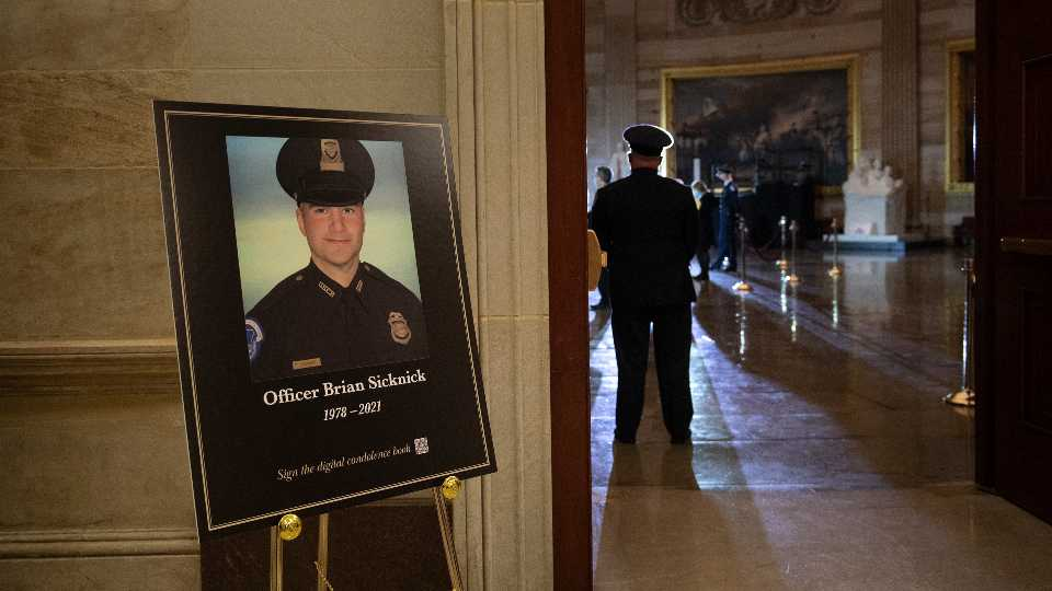 FILE - In this Feb. 2, 2021, file photo a placard is displayed with an image of the late U.S. Capitol Police officer Brian Sicknick on it as people wait for an urn with his cremated remains to be carried into the U.S. Capitol to lie in honor in the Capitol Rotunda in Washington. Federal investigators probing the death Sicknick, a U.S. Capitol Police officer killed in the Jan. 6 riot, have zeroed in on a suspect seen on video appearing to spray a chemical substance on the officer before he later collapsed and died, two people familiar with the matter told The Associated Press.