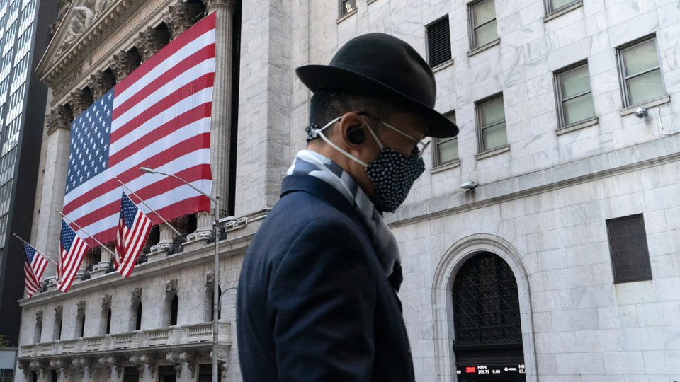 A man wearing a mask passes the New York Stock Exchange in New York