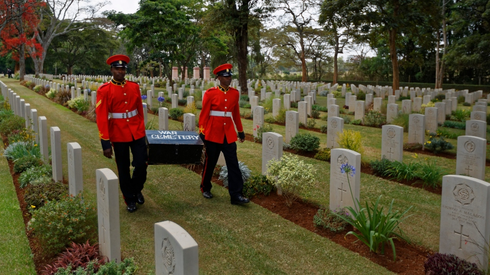 In this Sunday, Nov. 13, 2016 file photo, two members of Kenya's Military Police walk past graves as they leave after attending a Remembrance Sunday event, to honor the contribution of those British and Commonwealth military who died in the two World Wars and later conflicts, at the Nairobi War Cemetery in Kenya.