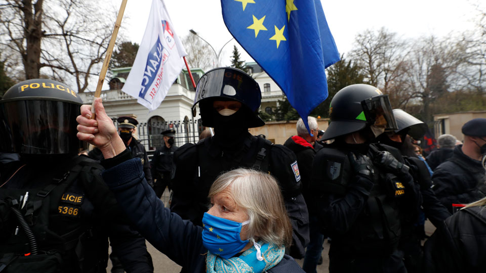 A woman waves a European Union flag in front of Russian Embassy