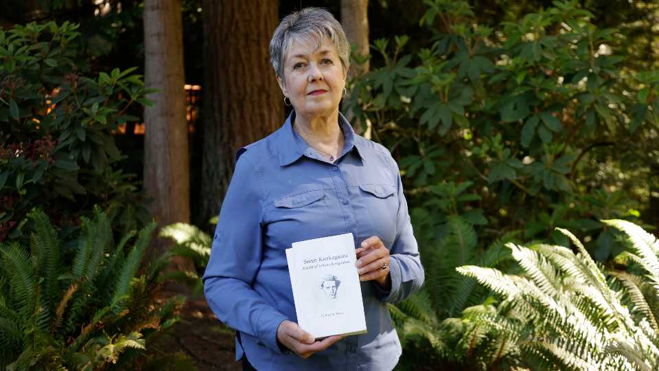 Karen McKnight stands in her backyard on Saturday, June 19, 2021, in Sammamish, Wash., holding two books written by her brother Ross Bagne of Cheyenne, Wyo. Nearly all COVID-19 deaths in the United States now are in people who weren't vaccinated like Bagne, a staggering demonstration of how effective the vaccines have been