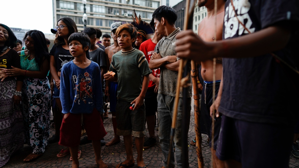 In this March 27, 2018, file photo, Indigenous people stand outside Sao Paulo's City Hall during a demonstration.