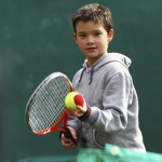 Little tennis player on a blurred green backround