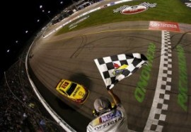 Joey Logano, driver of the #22 Shell-Pennzoil Ford, races to the checkered flag to win the NASCAR Sprint Cup Series Toyota Owners 400 at Richmond International Raceway on April 26, 2014 in Richmond, Virginia. Photo by Jeff Zelevansky/Getty Images