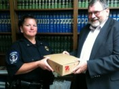 Prosecutor Holmes (right) hands Plymouth Police Deparment Corporal and Evidence Technician Bridget Hite a scale