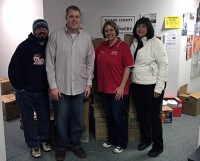 WKVI's Nathan Welter, Mitch Columbe, Mary Perren and Pulaski County Human Services Executive Director Jacki Frain with some of the food collected at Sanders Foods during the fifth annual WKVI Food Drive.