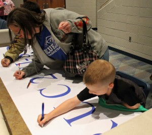 N.J.-S.P. Superintendent Lynn Johnson asked supporters of the corporation to sign a banner after the school funding presentation as a show of solidarity.