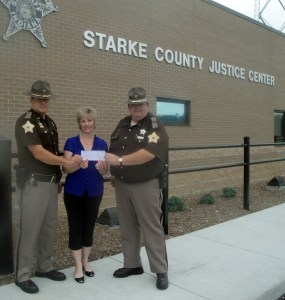 Communications/Marketing Director Amanda Steeb presents an Operation Roundup grant check to Chief Deputy Kenneth Pfost and Patrolman Robert Manning of the Starke County Sheriff's Office. Photo provided