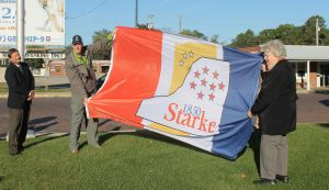 Starke Circuit Judge Kim Hall, Brad and Melba Shilling display the Starke County Flag on the courthouse lawn.
