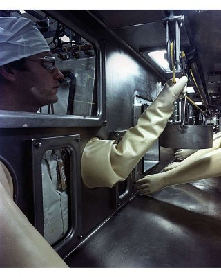 Technicians work on radioactive material in a protective box. Photo: Department of Energy