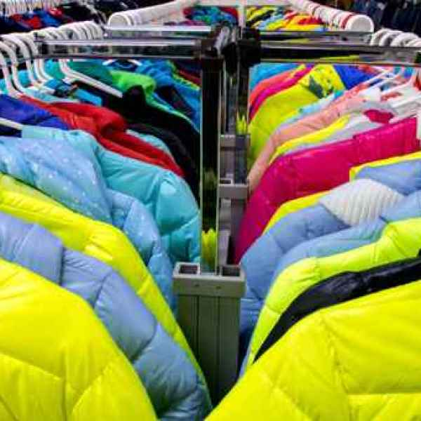 Variety of winter clothes on metal hangers. Colorful winter jack_524465