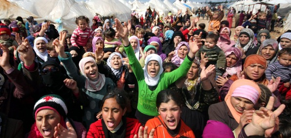 Syrian refugees, shown here at a protest rally, will soon be coming to American cities.
