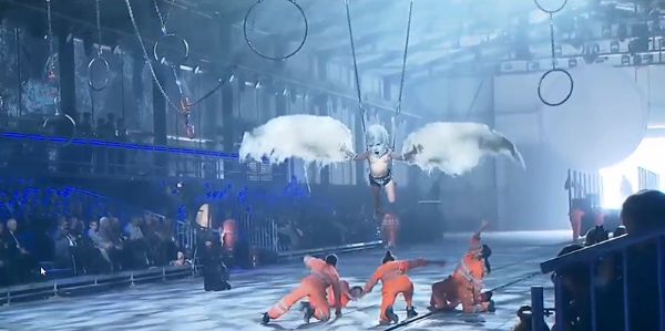 A fallen angel descends as five deceased workers are portrayed bowing before it.