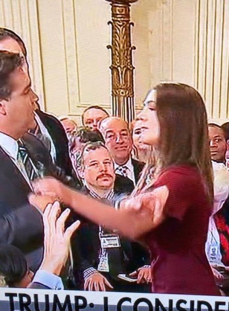 Jim Acosta grapples with a White House intern trying to take the microphone from him at a presidential news conference Nov. 7, 2018