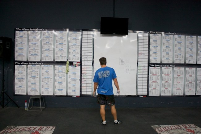 Un coach de crossfit prepare son tableau blanc