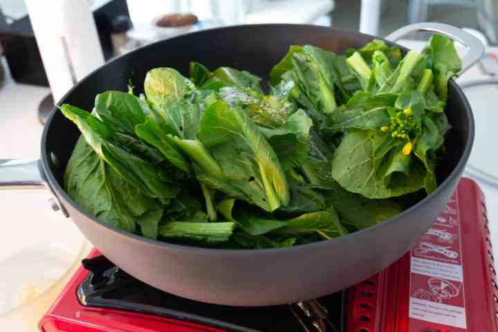 salt with jook choy leaves in a pan
