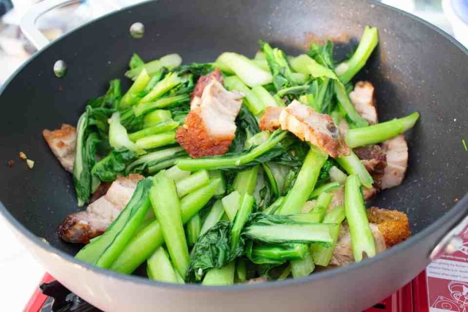 crispy pork belly and jook choy stir frying in a pan