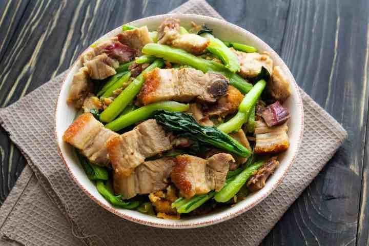 crispy pork belly stir fried with Asian greens on a dish