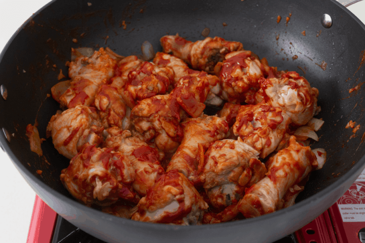Tomato puree covered over chicken drumsticks in a wok