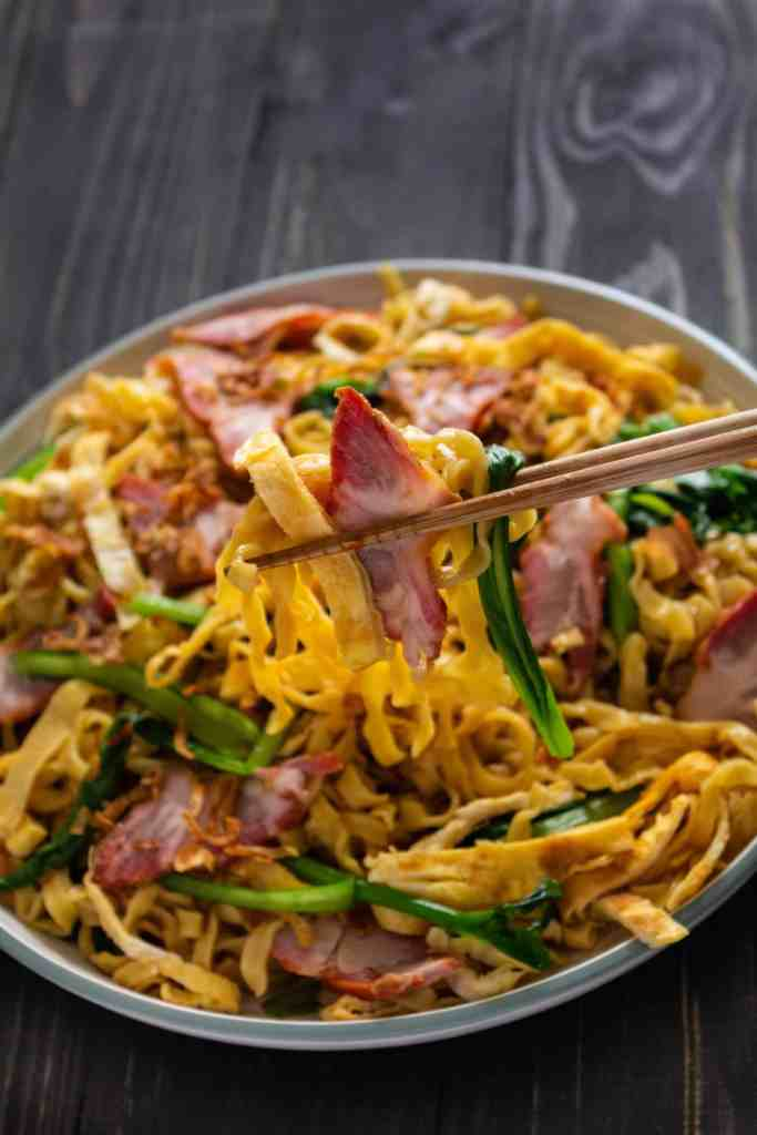 Egg noodles and bbq pork held up by chopsticks
