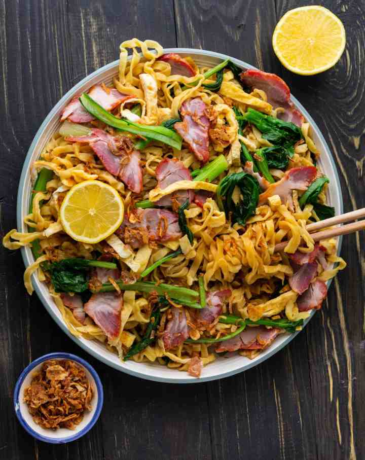 Egg noodles and bbq pork on a plate with chopsticks and lemon